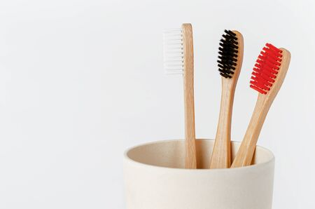 Red, white and black bamboo toothbrushes in eco cup on white background. Copy space, close up.