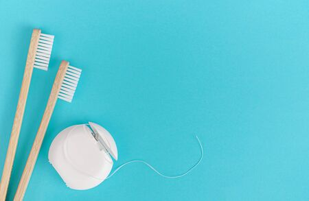 Bamboo toothbrush and dental floss on blue background. Copy space, overhead Zdjęcie Seryjne