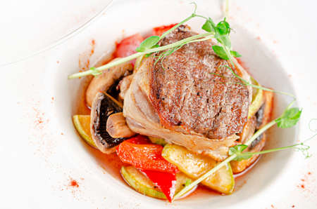 Veal steak with herbs and vegetables on white plate. Close up. Reklamní fotografie