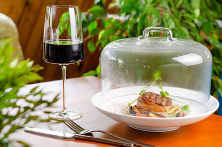 Glass of red wine and veal medallion with vegetables under transparent cap. Restaurant serving dish
