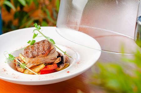 Veal medallion with vegetables on white plate. Restaurant serving dish Reklamní fotografie