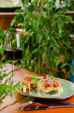 Trout fillet with tomatoes cherry and cheese, served with vegetables and red wine. Mediterranean lunch concept Reklamní fotografie