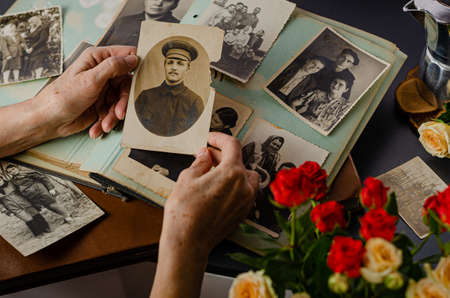 Cherkasy/Ukraine- December 12, 2019: Female hands holding and old photo of her grandfather. Vintage photo album with photos. Family and life values concept.