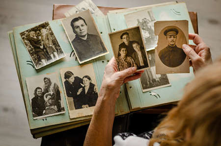 Cherkasy/Ukraine- December 12, 2019: Female hands holding and old photo of her relatives. Vintage photo album with photos. Family and life values concept.