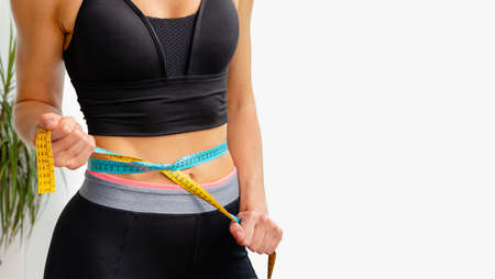 Young slim woman tightens measuring tape on her waist. Sporty lifestyle and weight loss concept. Copy space