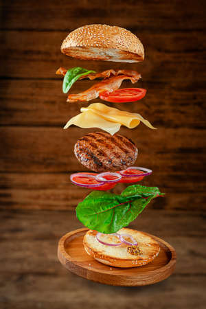 Flying hamburger with ingredients on wooden background. Creative still life concept Reklamní fotografie