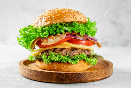 American food concept. Burger with beef and bacon on wooden plate on gray background.