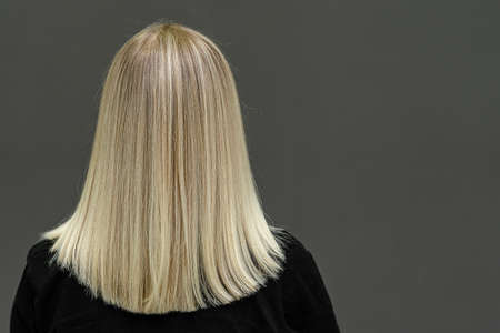 Blonde model with straight hair, look from behind. Hair lightening result. Copy space