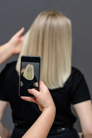 Hair stylist is taking a photo of models blonde after dyeing and hair straightening. Repair concept