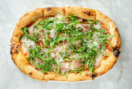 Prosciutto pizza or pinza with arugula in Roman style on marble background. Top view, overhead
