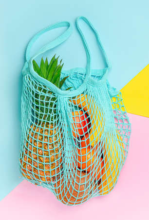 Different exotic fruits in reusable mesh bag on colorful background. Ecological lifestyle concept. Top view Imagens