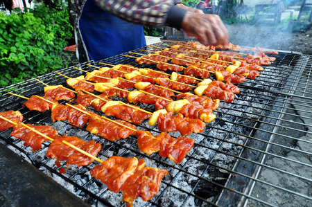 Smoky grilling the marinated pork meat delicious shashlik. Stock Photo