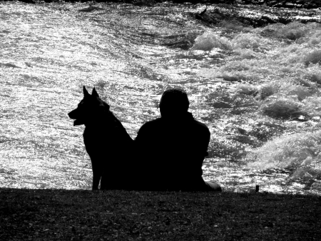 silhouette of a man and dog sitting on the river bank black and white photo