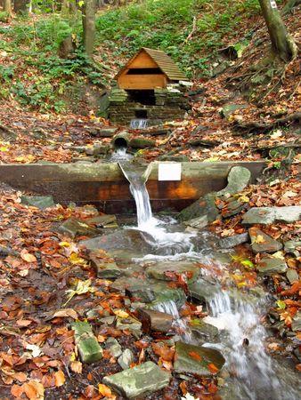 pozo de agua: arroyo de monta�a que fluye desde el pozo de agua Foto de archivo