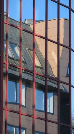 spiffy: reflection of a modern building in the windows of another building