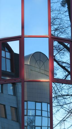 burnished: weird reflections of buildings and trees in several windows of a modern building