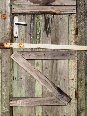 poorness: vertical photo of an old broken wooden door Stock Photo