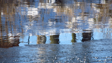 ice dam: partly frozen river with reflections on the water surface