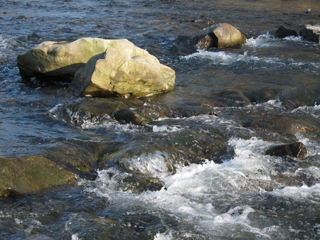 bubbling: clean river with some stones and bubbling water