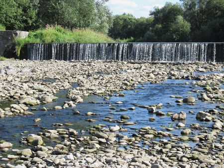 weir: weir on the river with low level of water and stones under it