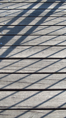 bannister: shadow of a bannister on the wooden gangplank Stock Photo