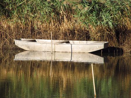 fishingboat: old fishingboat on the lake with beautiful reflections of plants