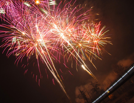 slantwise: photo of explosions of red fireworks taken obliquely