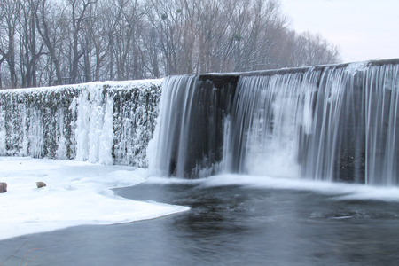 weir: water falling down from the weir with some icicles in winter Stock Photo