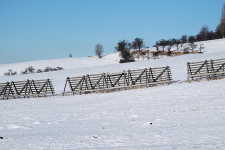 covered fields: winter landscape with wooden entanglements in the fields covered with snow Stock Photo