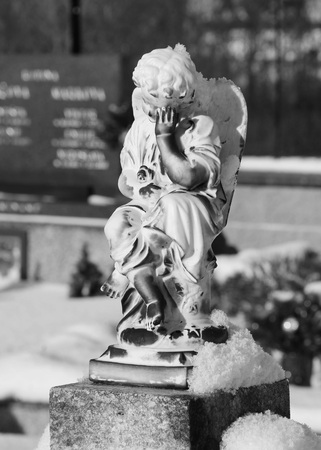 angel cemetery: black and white photo of a statue of sad angel on the cemetery