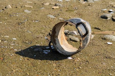 muddy: broken pot on the muddy bank of a pond