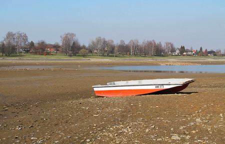 revealed: fishing boat on the revealed dry bottom of a pond Stock Photo