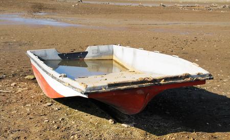 revealed: broken fishing boat on the revealed dry bottom of a pond
