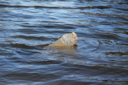 peeping: stone peeping out of the deep blue water