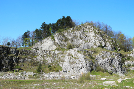 the former: rocks in former limestone quarry Kamenarka near Stramberk, Czech Republic with old stone walls under it Stock Photo