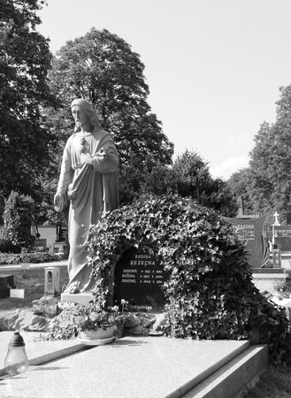 jesus standing: Nice sculpture of Jesus standing next to the grave on the cemetery in black and white