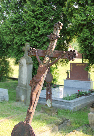 cross recess: old tilted rusted cross with Jesus on the cemetery Stock Photo