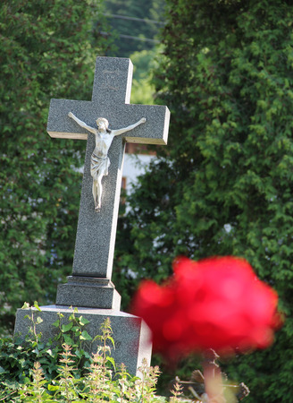 Old cross with Jesus and blurred crimson rose at the foreground