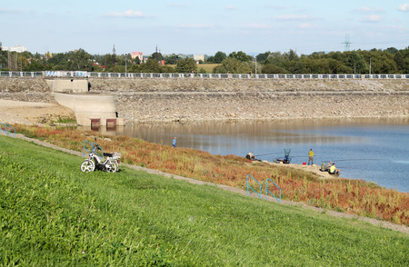 sear: group of fishermen on the bank of a drying dam with revelaed bottom covered with colorful plants in autumn