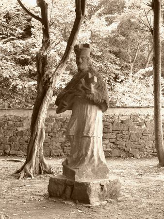 cross recess: photo of the old statue in the park in Vizovice, Czech Republic in ochre tones Stock Photo