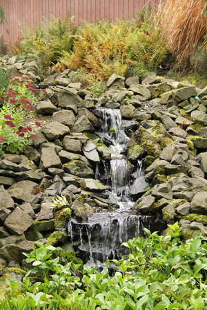 waterfall in the park with green leaves and partly sear fern around it in autumn Stock Photo