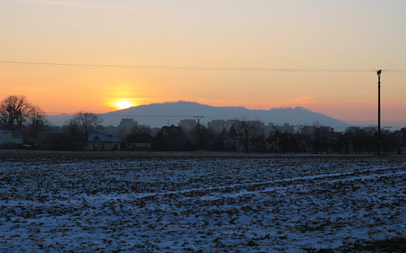 rural landscape with field covered with snow, pylon of electric wiring, some buildings and hills at the sunset