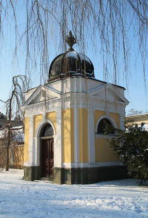 small white and yellow chapel under the twigs of bare willow in winter, Frydek-Mistek, Czech Republic Stock Photo