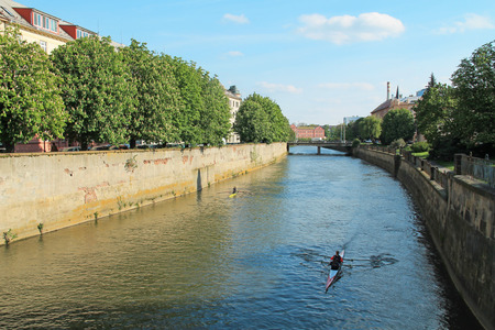 people paddling on the boats on Morava river on sunny spring day in Olomouc, Czech Republic