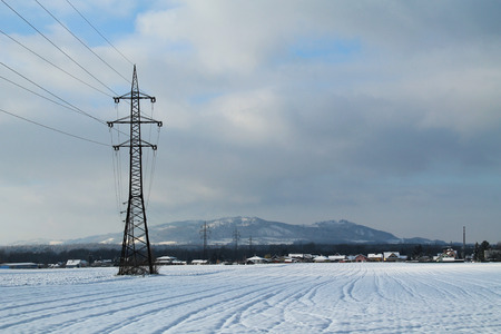 landscape with pylons of electric wiring in the fields in winter