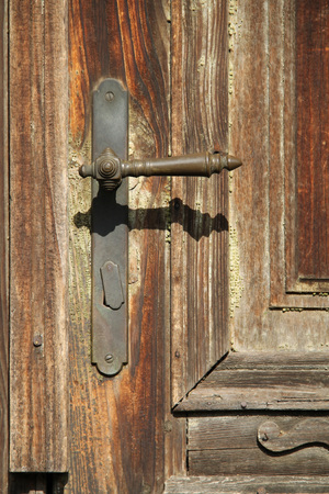close photo of a handle on the old wooden door of abandoned house