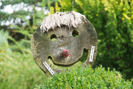 funny smiling face made of wood in the garden