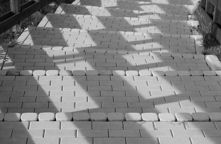 black and white photo of shadows on the stairs made of cobblestones