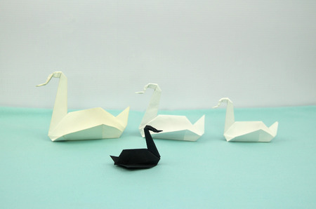 three white origami paper swans in the line and a small black one swimming against the flow