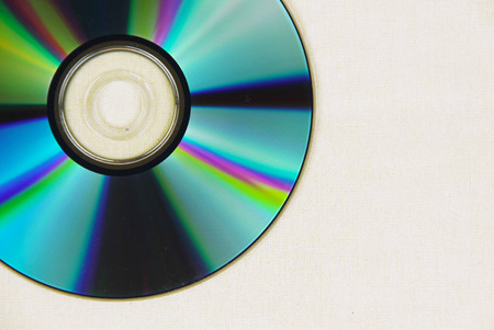 CD or DVD with beautiful colorful reflections laid on white cloth Stock Photo